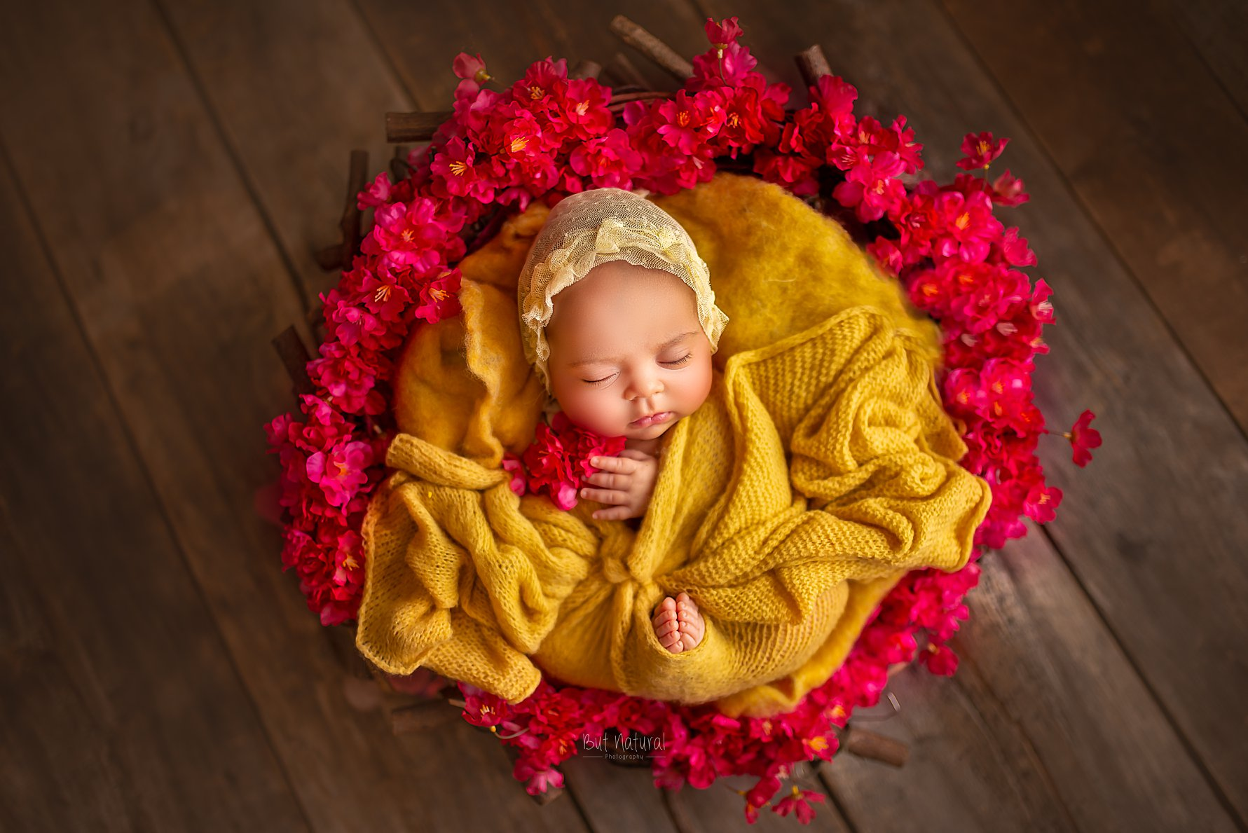 Newborn baby sleeping on a red coloured round-shaped flowered prop | But Natural Photography, Sujata Setia