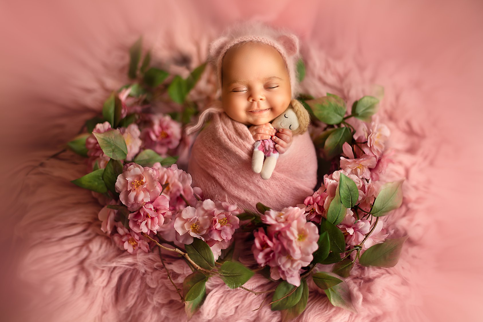 Newborn baby sleeping with a cute smile on a round-shaped flowered prop | But Natural Photography, Sujata Setia