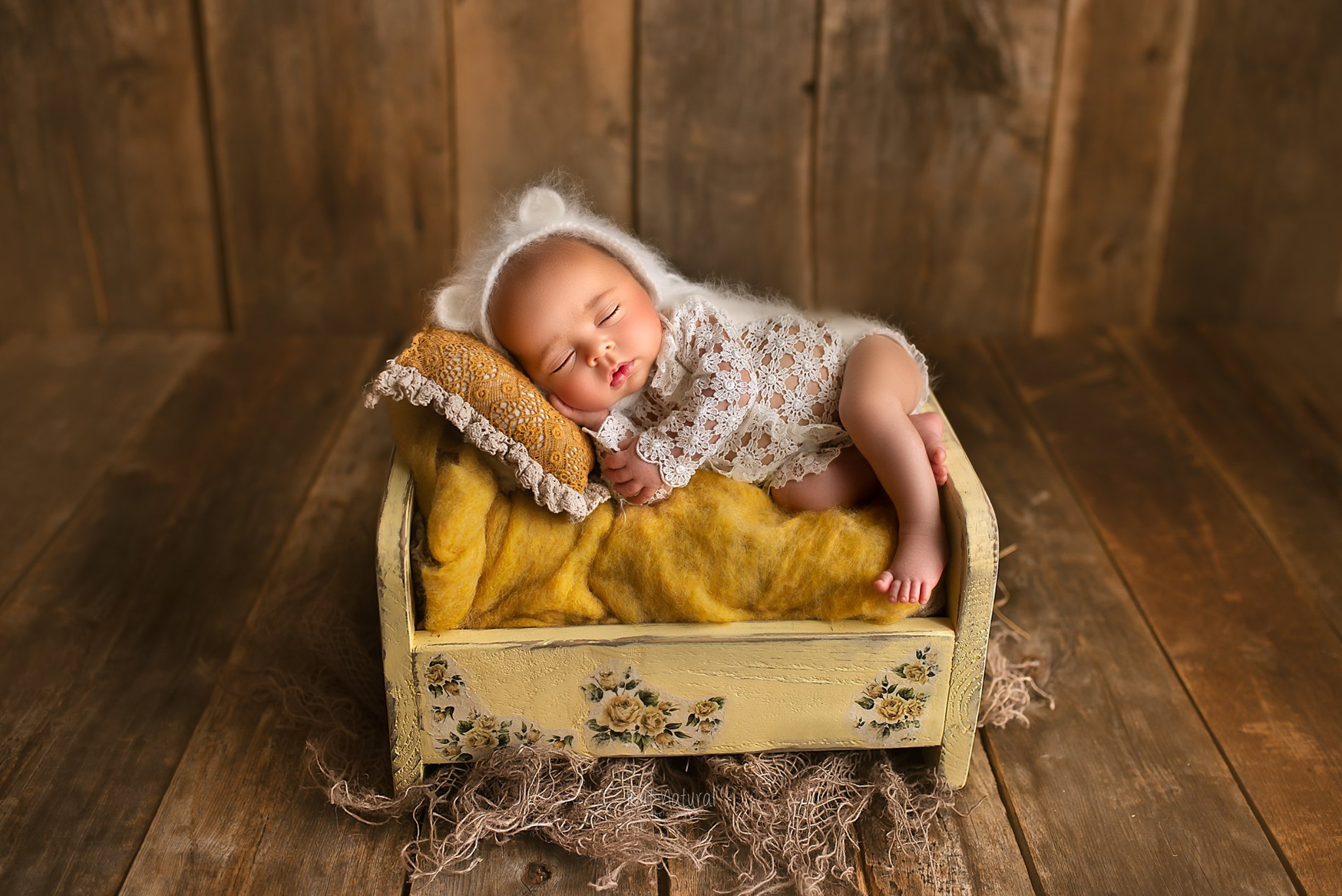 Newborn sleeping on a wooden bed prop for a newborn photography session by Sujata Setia | But Natural Photography