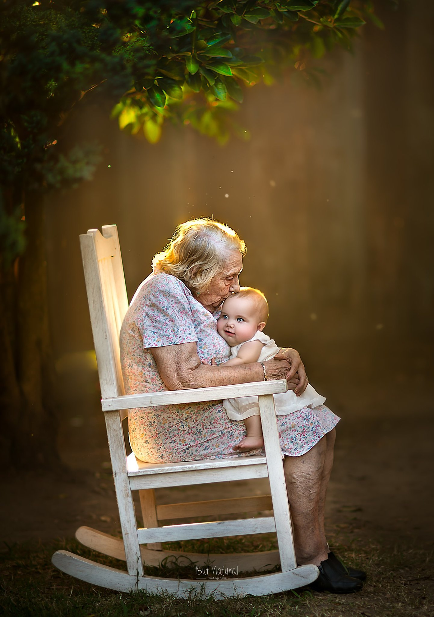 Grandmother kissing a cute little child on the forehead - But Natural Photography